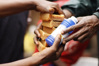An aid worker distributes soap and bleach in Guinea's capital, Conakry, where people have been infected with cholera.