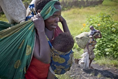 A woman and her family flee ongoing fighting between M23 rebels and government forces outside Sake, near Goma in the Democratic Republic of Congo.