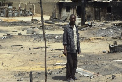 A man stands outside his destroyed home in Borno State, following heavy fighting between military forces from Nigeria, Niger and Chad, and Boko Haram.