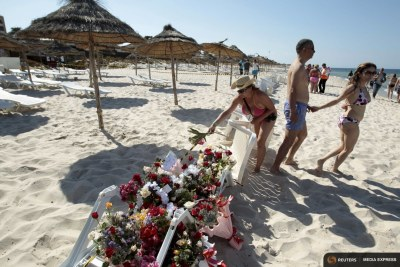 A tourist places flowers at the beachside of the Imperiale Marhabada hotel, which was attacked by a gunman in Sousse, Tunisia.