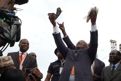 Amama Mbabazi releasing 'peace' doves into the air at Nakivubo stadium