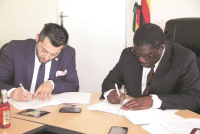 Industry and Commerce Minister Mike Bimha (right) signs a Memorandum of Understanding with the president of El Badaoui Group.