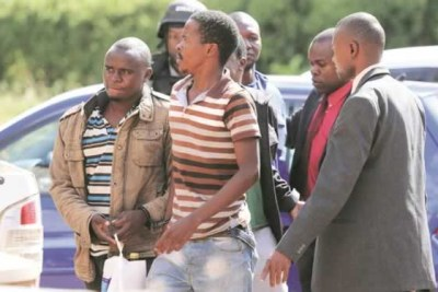 Two of the four suspects accused of trying to bomb Mugabe's Omega Dairy Farm being led away by detectives.