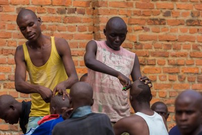 Men help to shave their colleagues. Accoring to Human Rights Watch, Gikondo Transit Center must be called a prison, there is unlawful Detention and Ill-Treatment in Rwanda's Gikondo Transit Center (file photo).