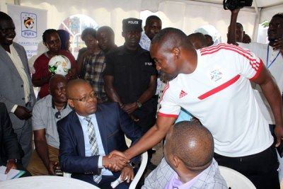 Friends or foes? Incumbent Fufa president Moses Magogo shakes hands with Mujib Kasule after both candidates picked nomination forms for Fufa presidency.