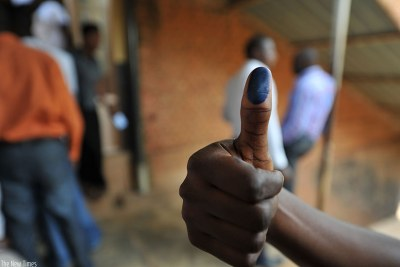 A voter shows his thumbs with ink after voting in a past election.