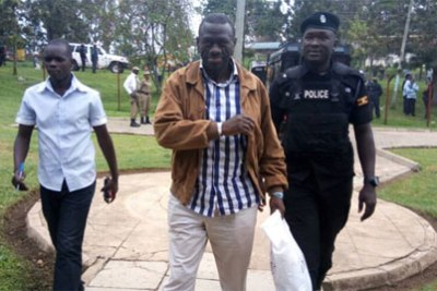 A policeman leads Dr Besigye to court.