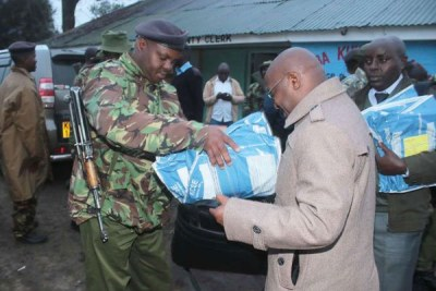 An administration police officer helps a school principal carry KCSE examination papers at Gilgil Sub-County offices in Nakuru on November 13, 2017.