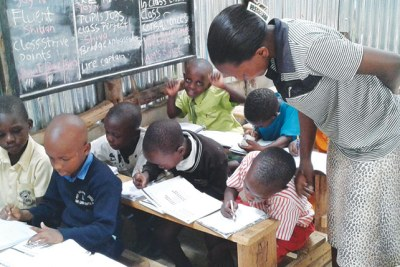 A teacher attends to learners at Bridge International Academy, Katooke