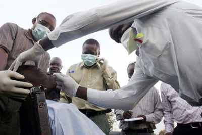 Health officials examines a patient after a Swine flu scare in Kisumu (file photo).