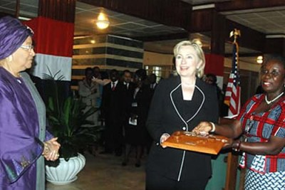 Hillary Clinton is given the keys to Monrovia, a symbolic welcome for foreign dignatories. President Johnson Sirleaf is at left.