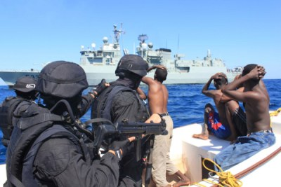 Portuguese marines and apprehended Somali pirates approach a warship.