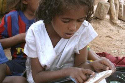 Une petite fille malienne au Burkina Faso qui apprend à l'école.