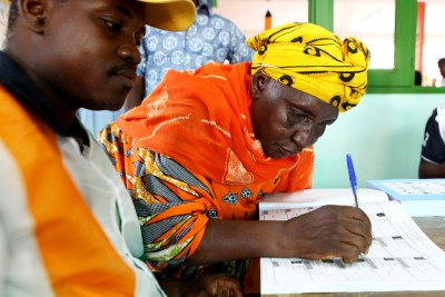 A woman signs a document certifying her vote in Côte d'Ivoire's legislative elections, at a polling station in Bondoukou.