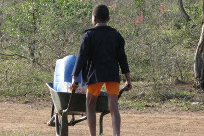 South Africa: A child pushes a wheelbarrow carrying water containers.