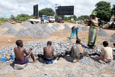 A woman watches children working at a stone quarry, Zambia, in March 2007