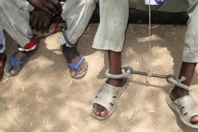 Détenus de la prison d'Abéché portant des entraves métalliques aux chevilles.