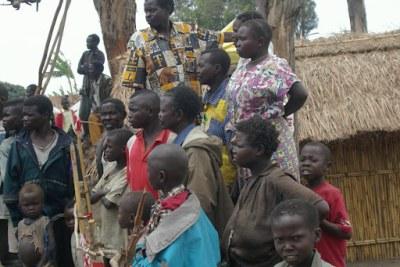 A coté de leur maison d'habitation, les membres d'une même famille suivent le passage du cortège du gouverneur du Nord-kivu, lors de sa première visite officielle à Rutshuru après le conflit.