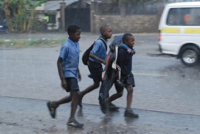 A group of schoolchildren fight against the rain to get home (file photo).