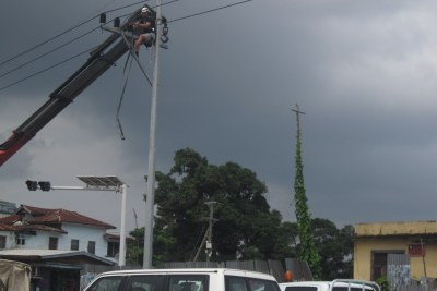 Workers of the Liberia Electricity Corporation planting a metal pole in Monrovia.