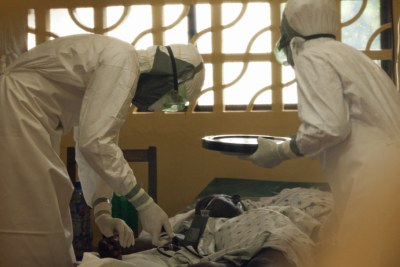 Dr Kent Brantly cares for an Ebola patient in the isolation ward before he tested positive for the virus.