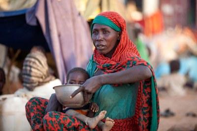 Une mère déplacée prépare de la nourriture pour son enfant près d'une base de la MINUAD à Um Baru, dans le Nord-Darfour.