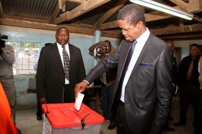 Le président Edgar Lungu de la Zambie glissant son bulletin dans l'urne.