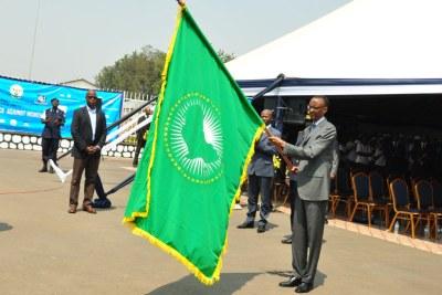 Le Président Kagame portant le drapeau de l' Union africaine.