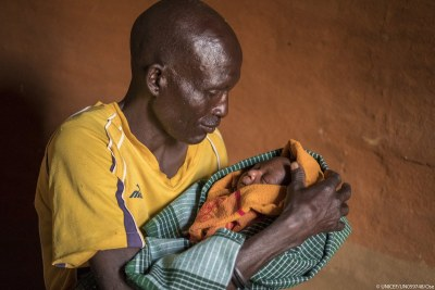 "Nachadee Lokwabong, 50, holds his one-week-old son Enoch Rofich for the first time at home in the Amudat district of Karamoja, Uganda, 15 March 2017. ""I am happy,"" says Nachadee as he looks down at his newborn son and strokes his cheek."