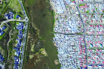 An aerial view of a gated community in Cape Town South Africa, left  directly adjacent to Masiphumelele township (right).