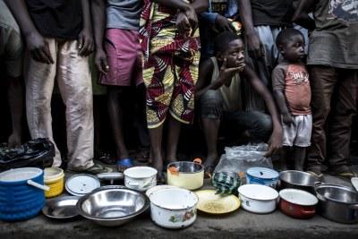 Des familles congolaises déplacées de la province du Kasai font la queue pour obtenir de la nourriture dans les locaux d'une ancienne clinique de ville d'Idiofa, après avoir fui la violence près de leurs villages