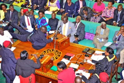 Aruu County MP Samuel Odonga Otto jumps on to the table to grab the microphone from Bukholi Central MP Solomon Silwany during the age limit debate in Parliament on Tuesday.