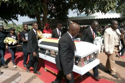 Staff of Kampala Funeral Directors carry the casket containing the body of singer Mowzey Radio.