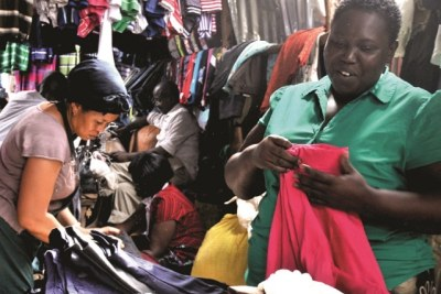 Jessica Kiyingi, a vendor at Kampala's Owino market, selling second-hand clothes.