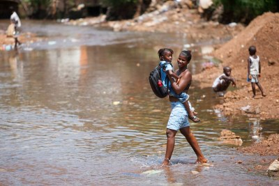 A mother carries her child across the filthy water in a slum town in Congo Town Community.