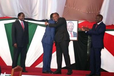 President Uhuru Kenyatta hugs Opposition leader Raila Odinga as his Deputy President William Ruto (right) and Wiper leader Kalonzo Musyoka cheer them (file photo).
