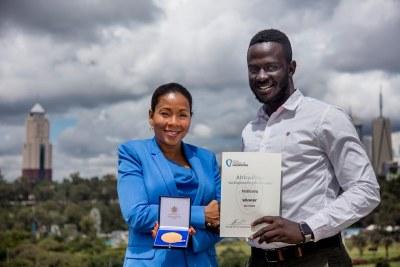 Africa Prize judge Rebecca Enonchong presents Ugandan Brian Gitta of Matibabu with the Africa Prize winner's medal.