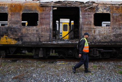 Metrorail official walks passed a charred train carriage in Cape Town last week. It is one of several carriages damaged in arson attacks in recent weeks.