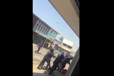Video screenshot of eSwatini officers beating a worker during a protest.