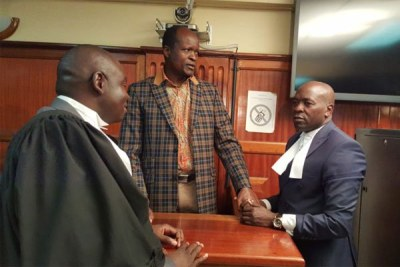 Migori Governor Okoth Obado speaks with his lawyers at the High Court in Nairobi on October 12, 2018.