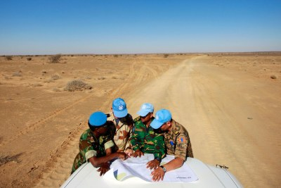 Peacekeepers with the UN Mission for the Referendum in Western Sahara (MINURSO) consult a map as they drive through vast desert areas in Smara, Western Sahara.
