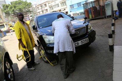 Nairobi City County attendants clamp a car whose owner had not paid for parking (file photo).
