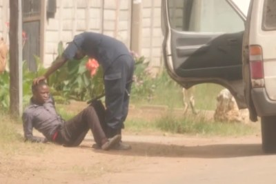 A screenshot from a Sky News video of a man being beaten by security forces.