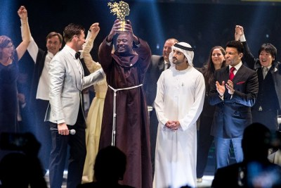 Cette image fournie le 24 mars 2019 par le Global Education and Skills Forum, une initiative de la Fondation Varkey, montre l'enseignant kenyan Peter Tabichi (au centre) brandissant le trophée du Global Teacher Prize (GTP) après avoir remporté le prix d'un million de dollars une cérémonie officielle à Dubaï présentée par l'acteur australien Hugh Jackman (centre-gauche) et à laquelle assistait le prince héritier de Dubaï Hamdan bin Mohammed Al-Maktoum (centre-droite).