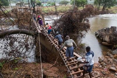 Les habitants traversent un pont de fortune à Copa où 63 maisons ont disparu sous la boue et les rochers amenés en aval par les pluies torrentielles du cyclone Idai. 38 autres maisons ont été endommagées. Les résidents estiment qu'environ 200 personnes ont été emportées au Mozambique. Un seul des corps retrouvés a été identifié.