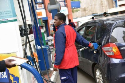 A pump attendant fuels a customer's car in Nairobi (file photo).