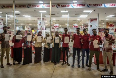 Staff of Sena supermarket hold signs supporting the revolution while refusing to work during a strike in Khartoum, Sudan, May 28, 2019.