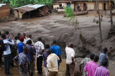 Survivors look on as flood waters pass through homes in a village in Uganda's Bududa district.