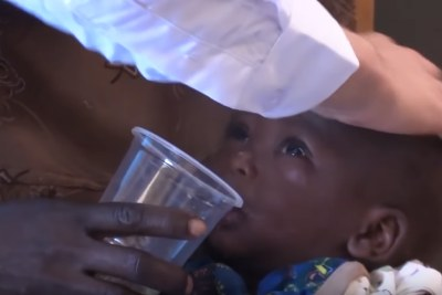 Video screenshot of an infant being given chlorine dioxide, an oxidizing agent used in bleaching.