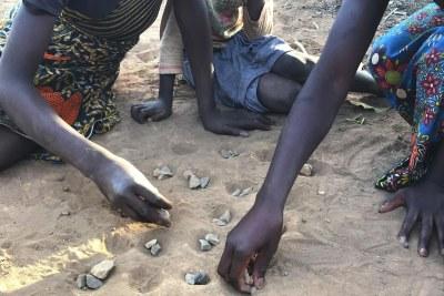 Trois jeunes filles jouent avec des cailloux en guise de pions (jeu « isolo ») sur un terrain sableux dans la commune de Waya à Kabwe, en Zambie. Or, elles s'exposent ainsi à des poussières de plomb toxique, dont les taux sont particulièrement élevés dans les sols de cette zone.